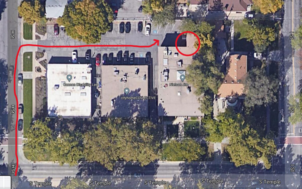 Pictured is a google map screenshot showing an overhead of the firm's building and parking lot with an arrow showing how to enter the parking lot. The door that should be used to enter is circled.