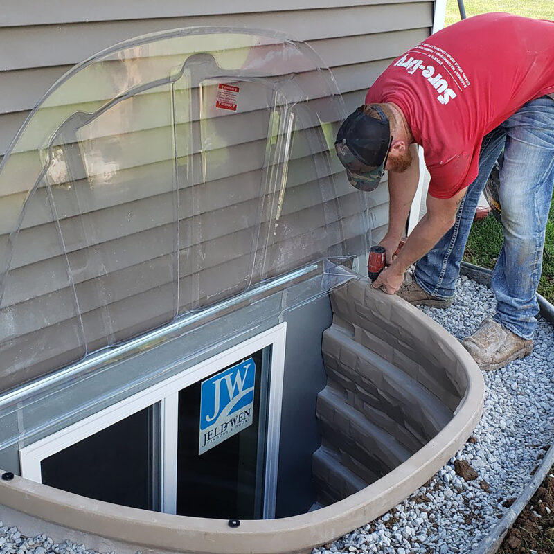 Person installing a DuraWell Egress Window Well Cover