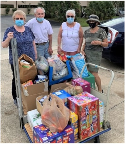four people wearing covid-masks standing behind load of food donations