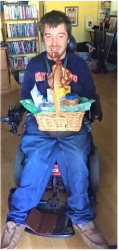 scott, dressed in blue, in wheelchair, holding gift basket