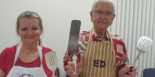 woman and man with aprons holding up spatulas