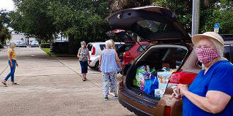 a few foks in parking lot next to cars loaded with food collection