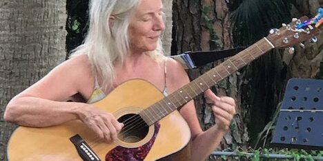 woman playing guitar and singing