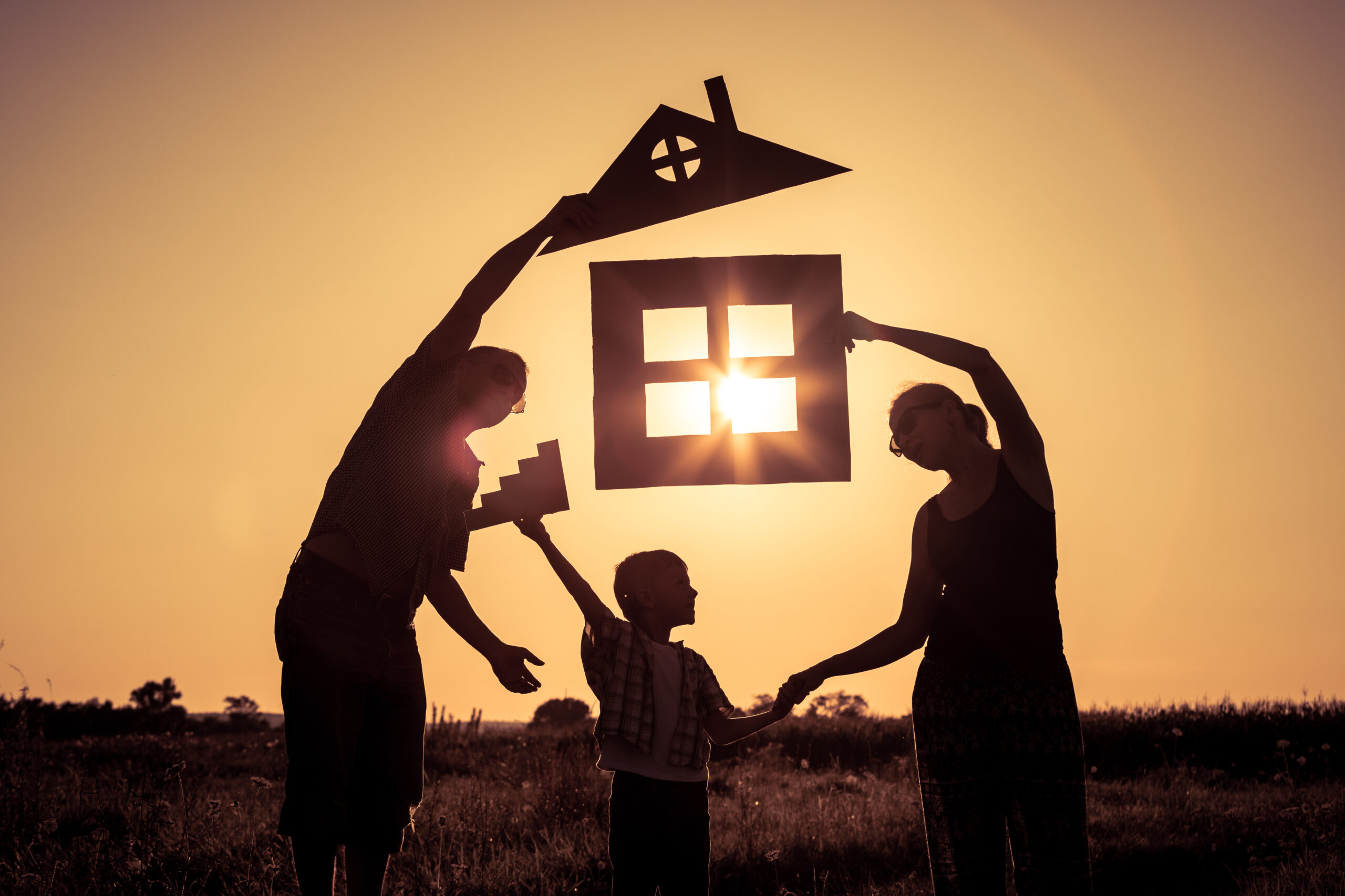Stock photo of a family holding a cutout of a house with the sun shining through it.