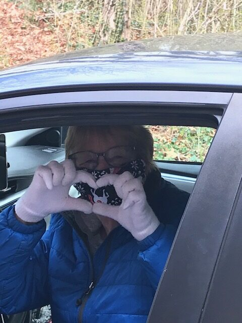 Housing Assistance Volunteer Susan Gilbert holds her hands in the shape of a heart after dropping off food from the Falmouth Service Center to our Carriage House Shelter