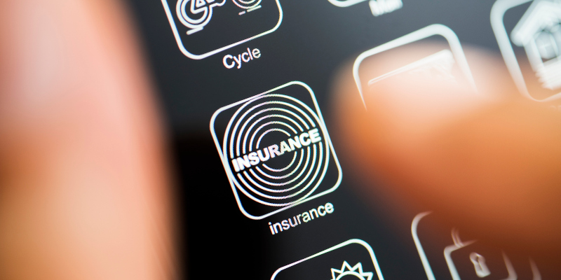 White app logo on black screen. Hand holding phone with insurance app on dark mode screen.