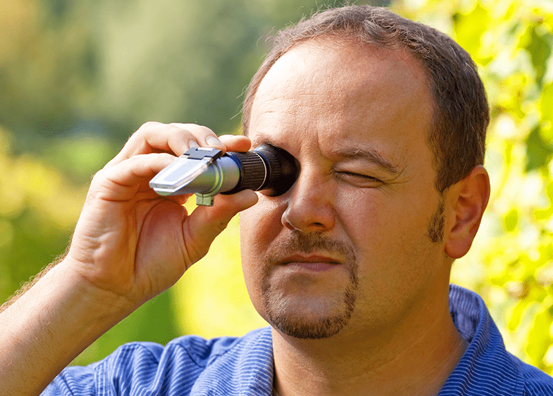 Guy demonstrating how a refractometer works.