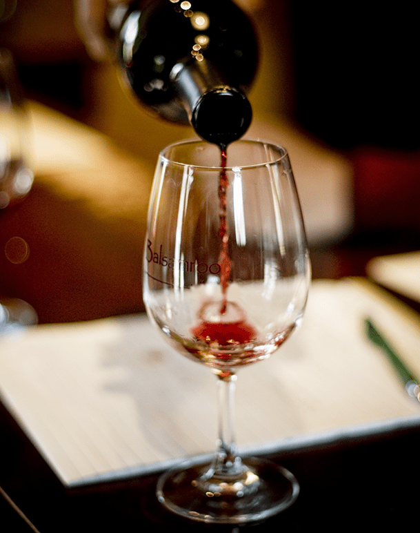 Wine Pouring Into Glass With Notes
