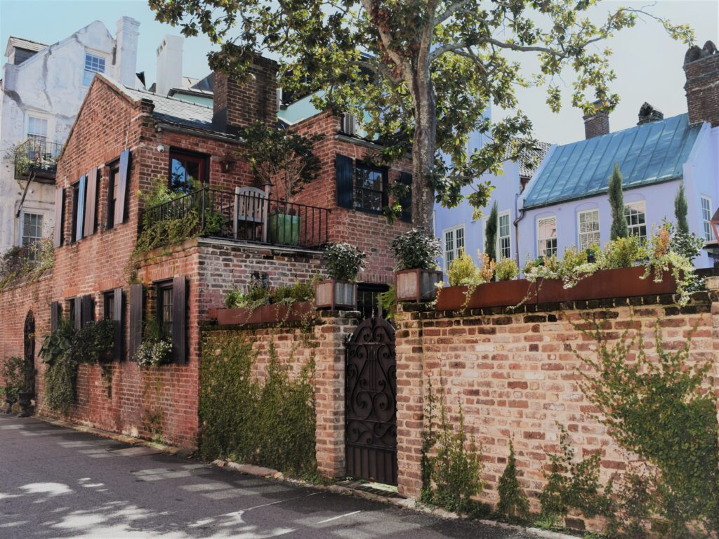 charleston south carolina southern historic travel red brick house old vines alley terrace balcony patio downtown black shutters plants foliage