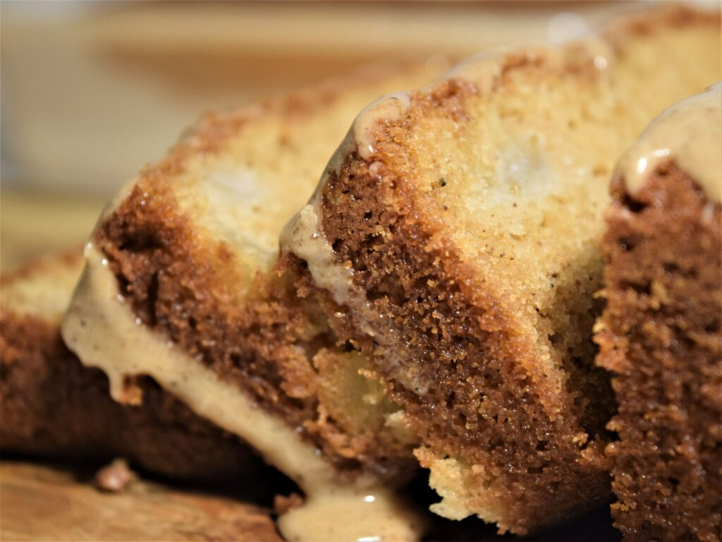 close up vanilla chai pear bread slices spice icing glaze dripping warm browns cozy baking