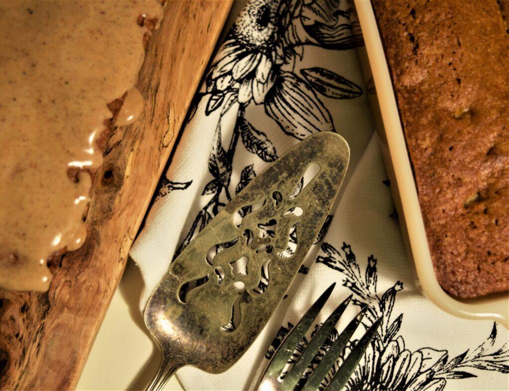 close up vanilla chai pear bread spice icing glaze silver pie server vintage warm browns cozy baking board fire king
