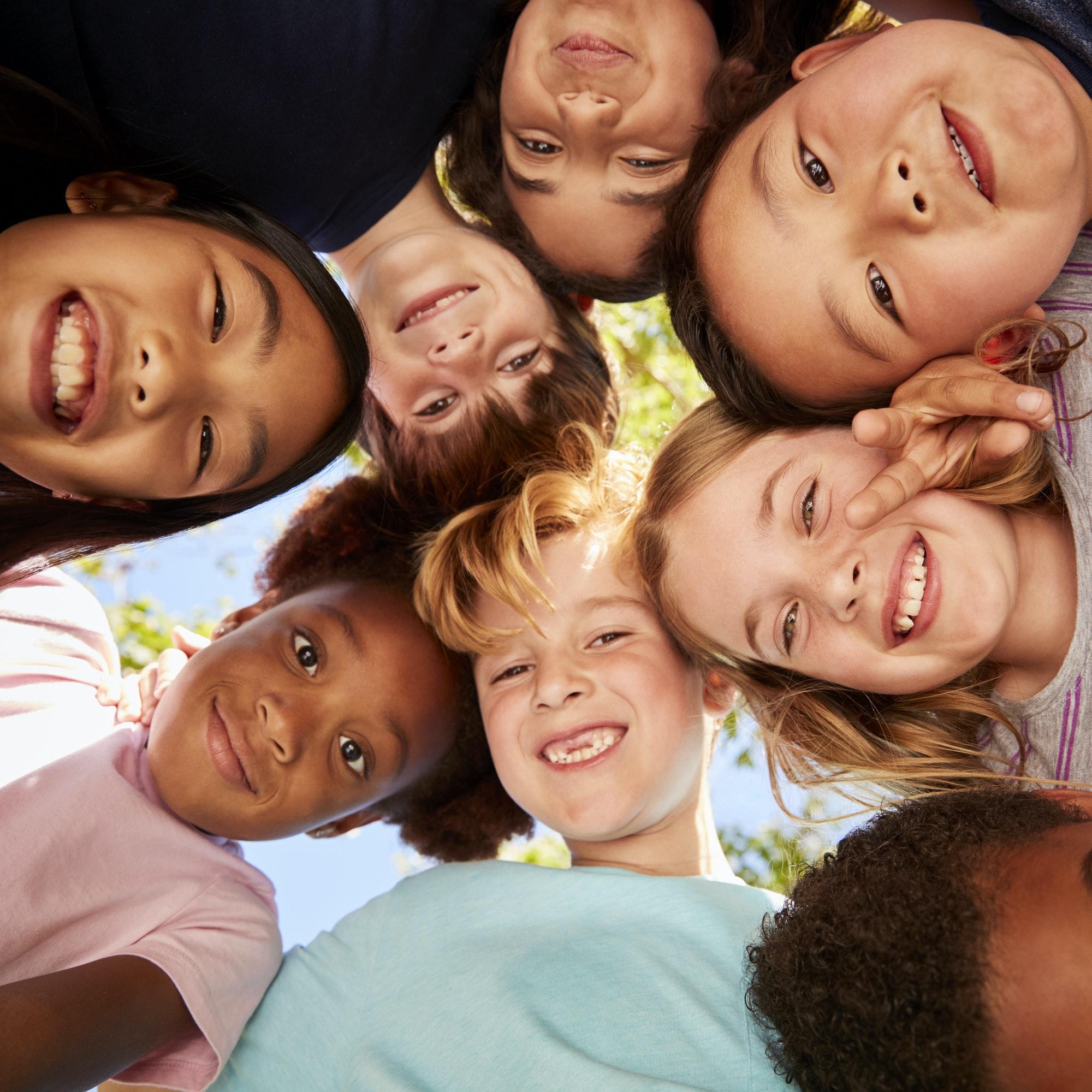 A huddle of school kids looking down at camera, close up