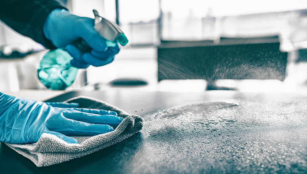 A Pandemic Solutions technician demonstrates the use of a backpack electrostatic sprayer in a kitchen (courtesy of Pandemic Solutions).