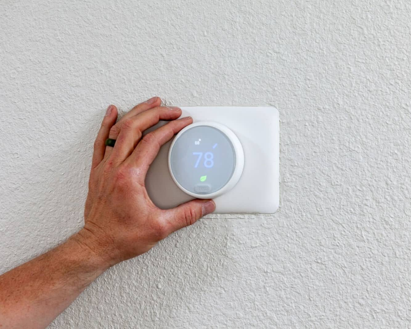 A hand turning a Nest Thermostat