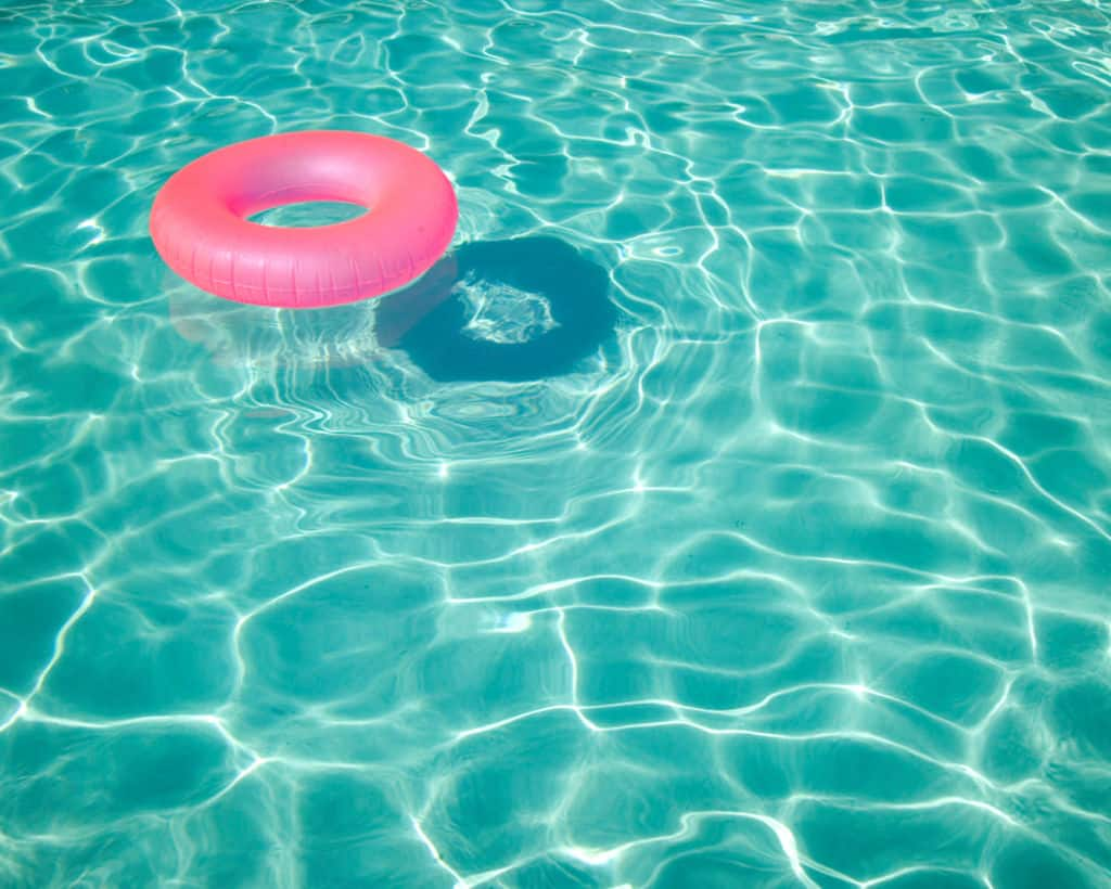 Pink inflatable donut floating in pool water