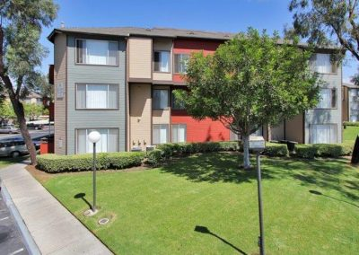 River House Apartments facade with grass and trees