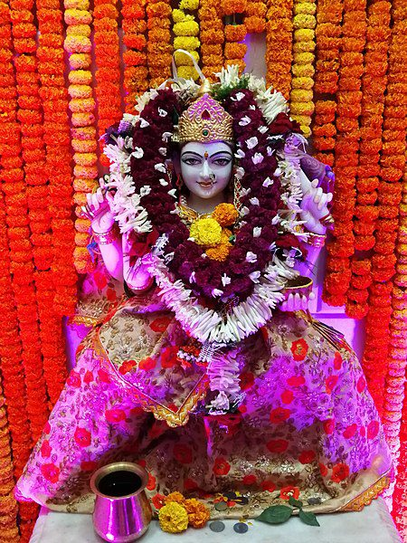 The Hindu goddess Santoshi Mata in a crown, magenta and red robes, with burgundy and white garlands around Her neck, against a background of marigolds.