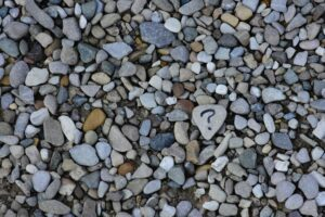 lovely array of grey brown, blue, white stones filling the photo with one near the center with a question mark on it