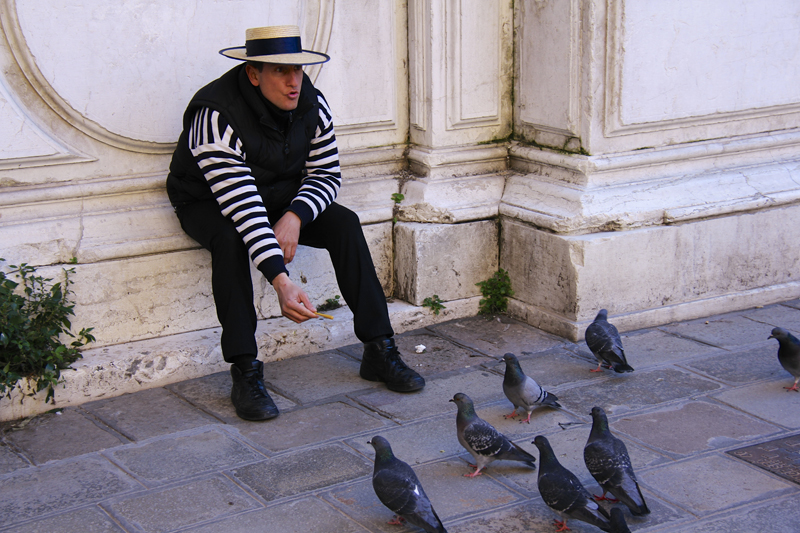 A gondolier takes a break to feed his friends