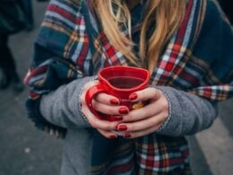 A girl wearing a scarf and holding a cup of tea