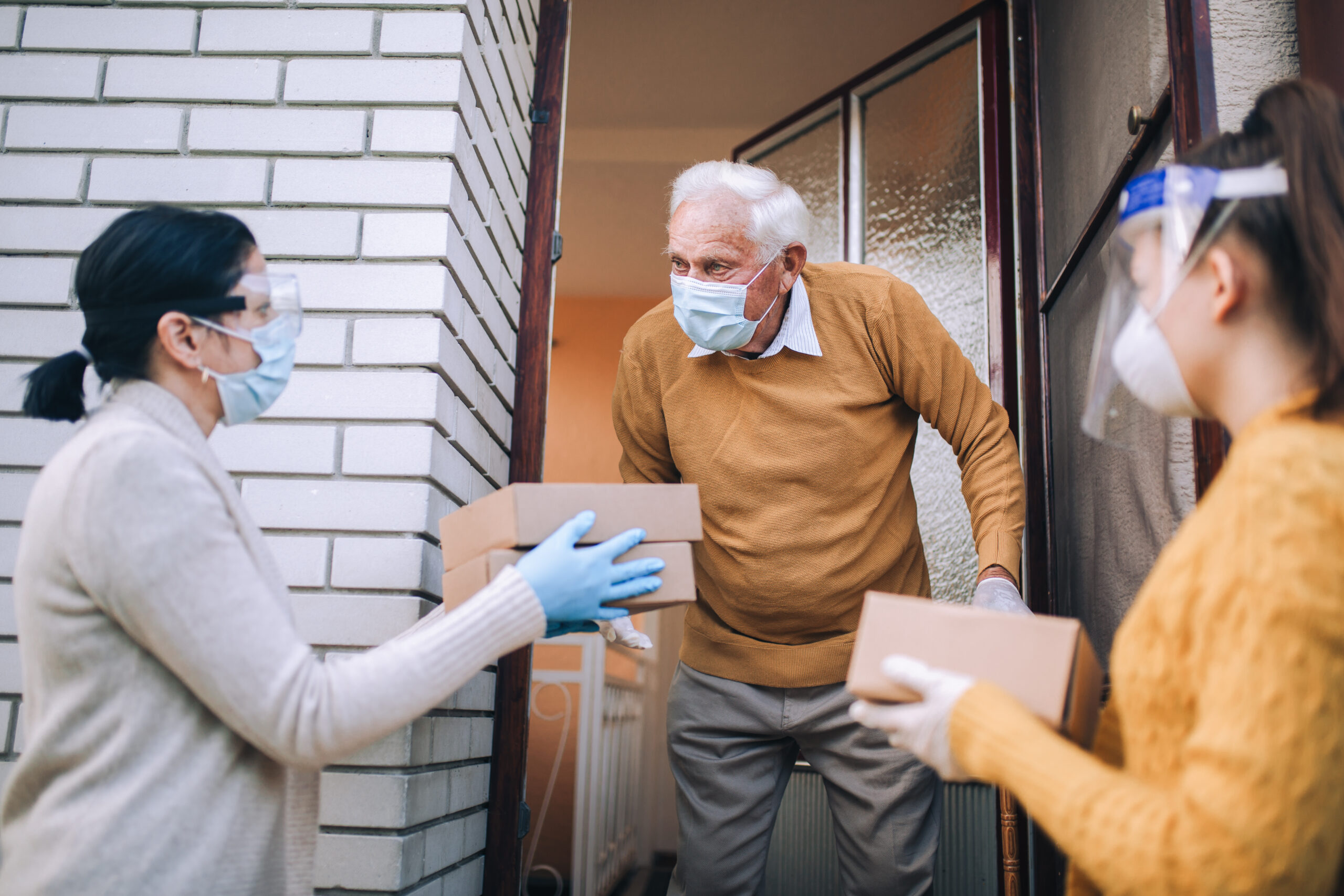 women delivering to elderly person