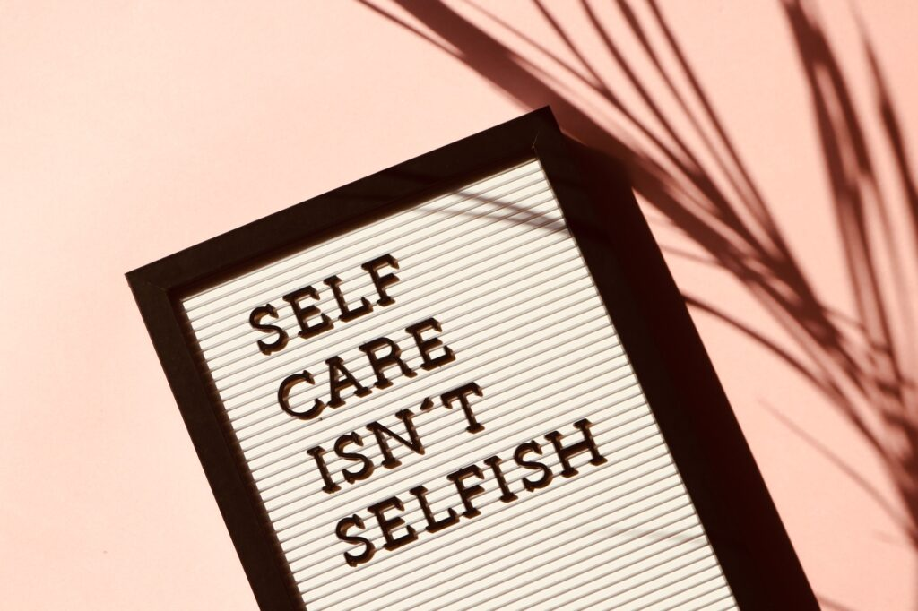 "A white letterboard with the words, ""self care isn't selfish"" on it with a black border in the foeground to a room that has the shadow of a large fern in the back ground"