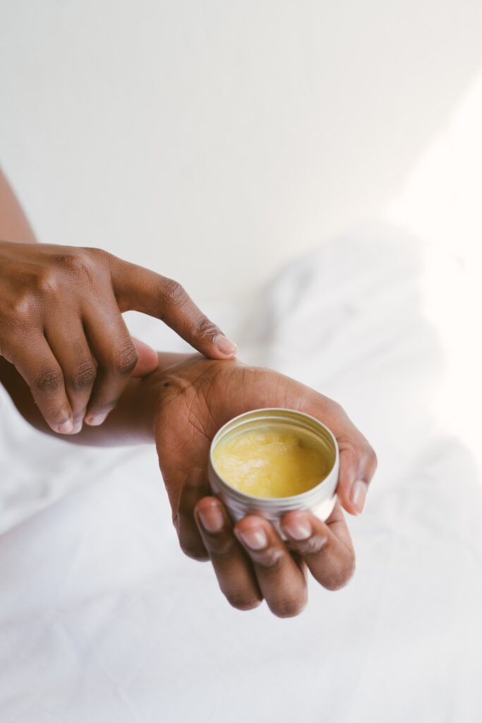 upclose graphic of a black woman applying salve to her hands while holding a tin can of an ointment.