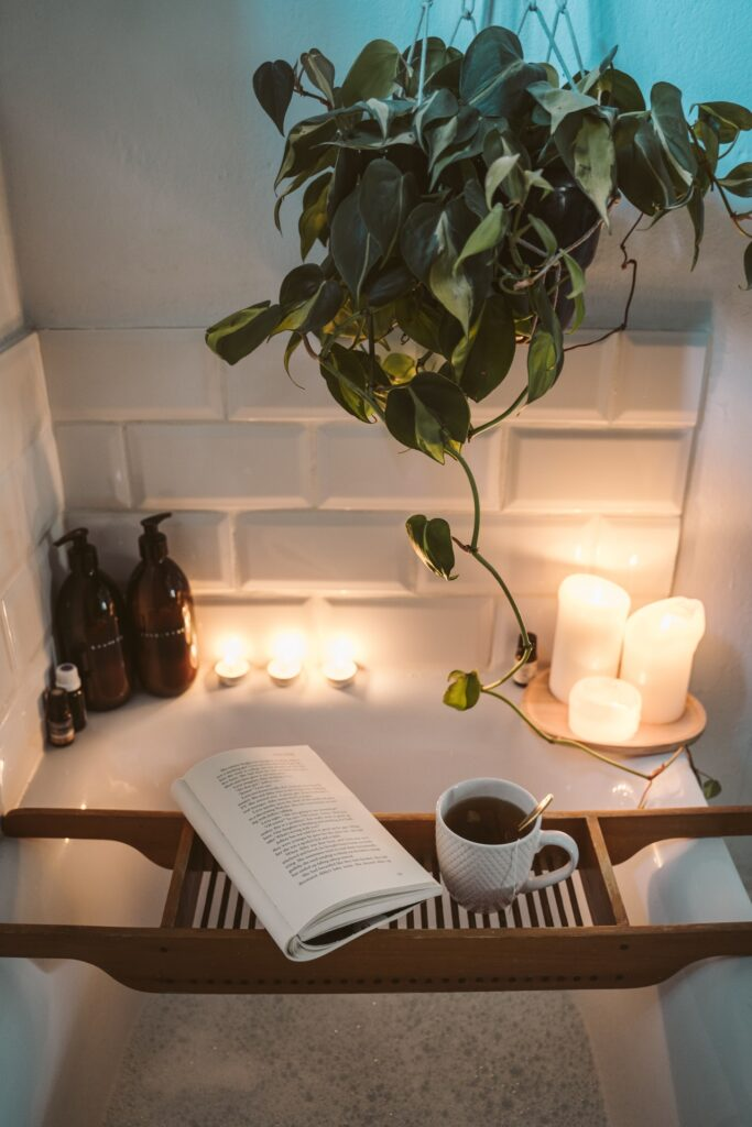 photo of a soothing bath with a book and tea and candles