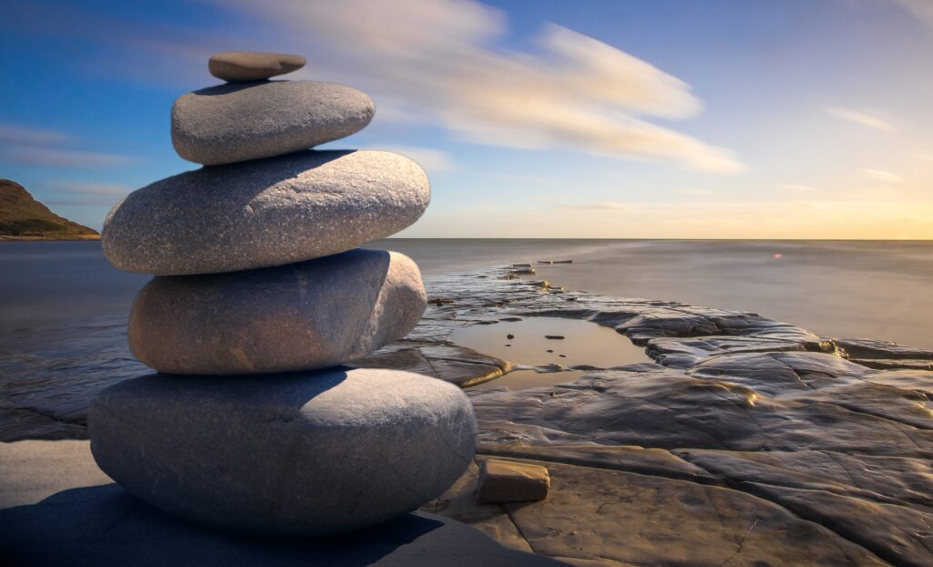 photo of rocks piled up on a ledge overlooking the shoreline during dawn or dusk