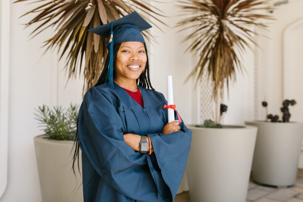 recent graduate in a blue cap and gown holding diploma