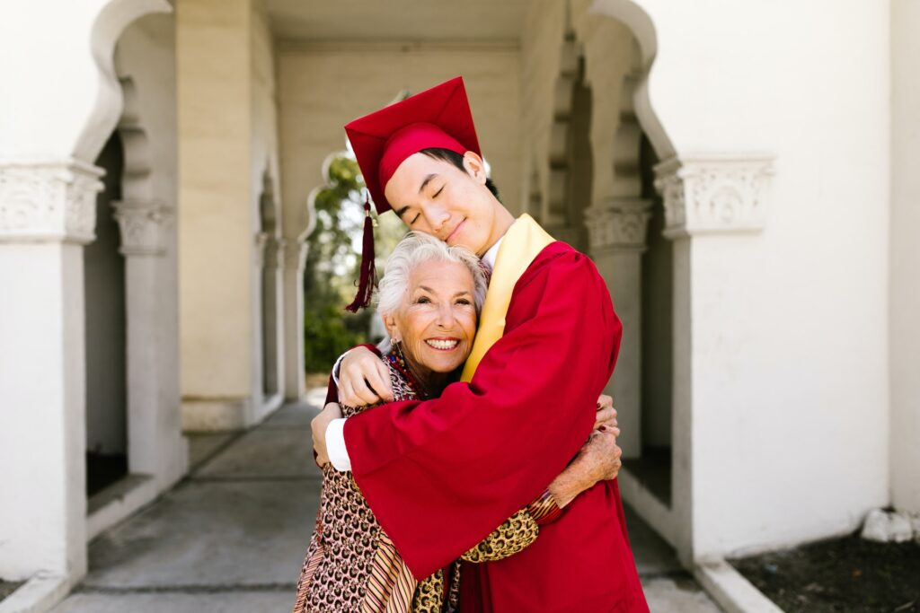 grandmom hugging grandson in red cap and gown