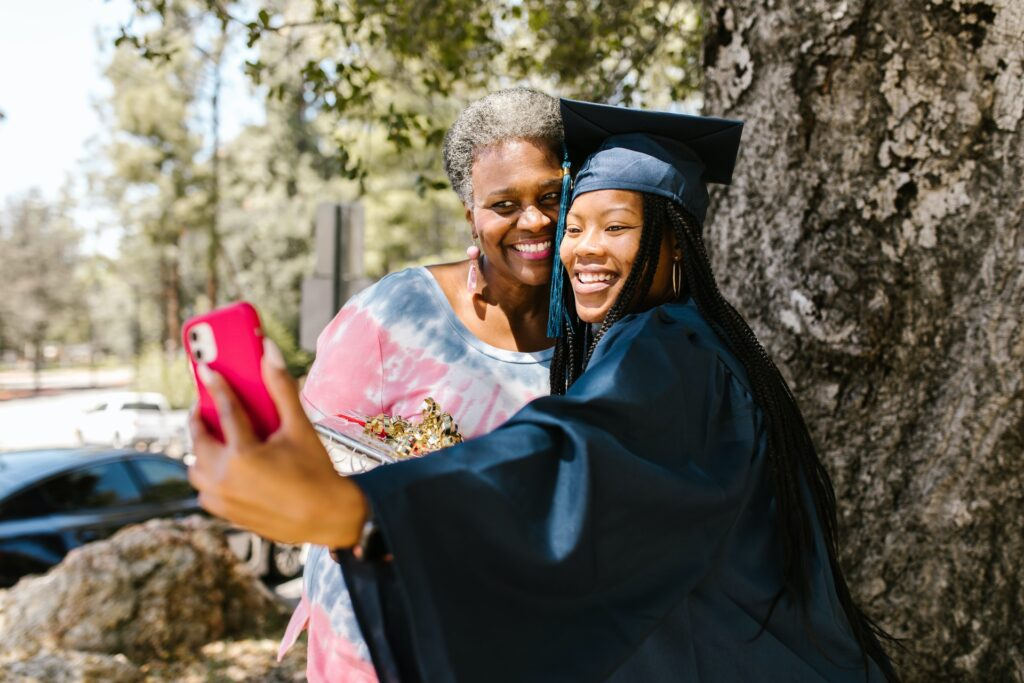 mom taking photo with daughter in cap and gown