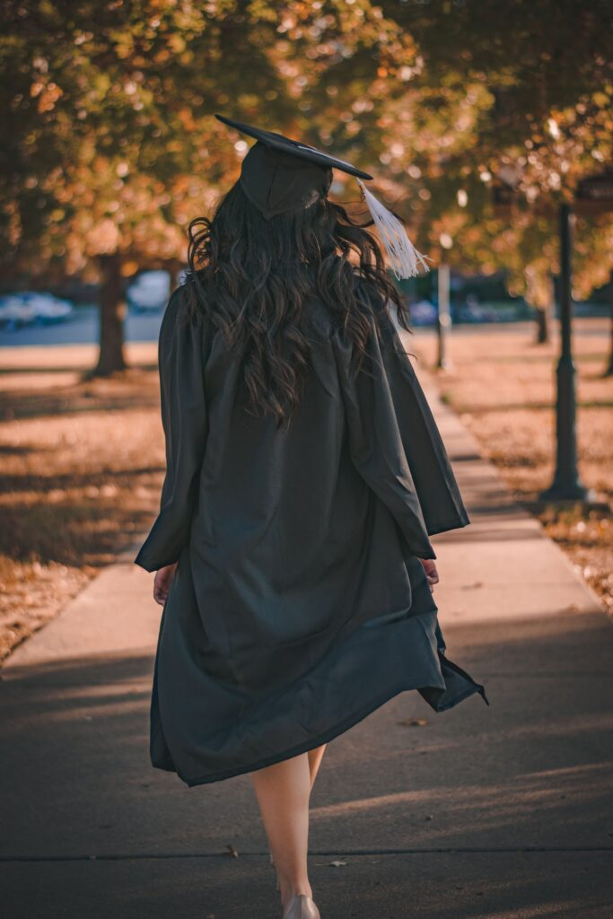 graduate in cap and gown walking away