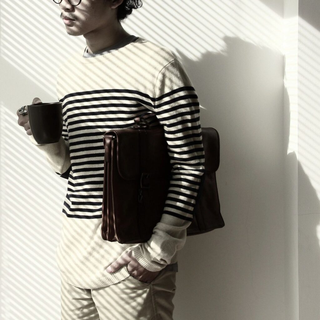 man with a brown leather briefcase under his arm and a coffee cup in another standing against wall with sunlight from blinds reflecting on his face and body.