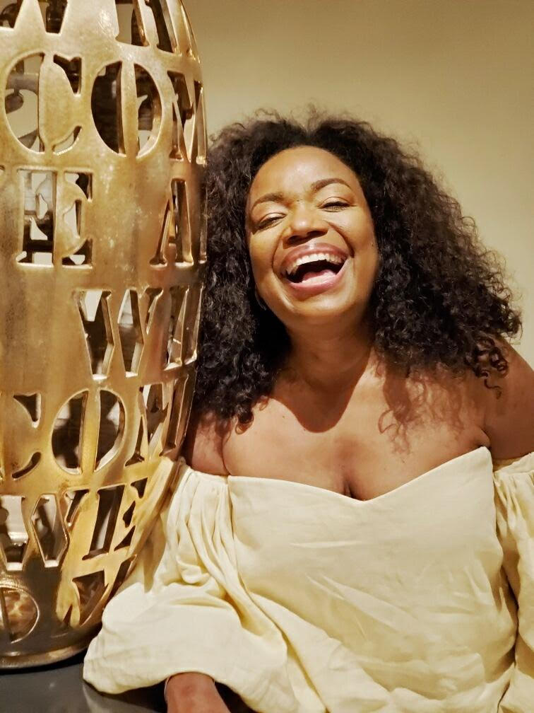 photo of Nicole Commissiong, black woman with curly hair in a yellow off the shoulder blouse smiling big