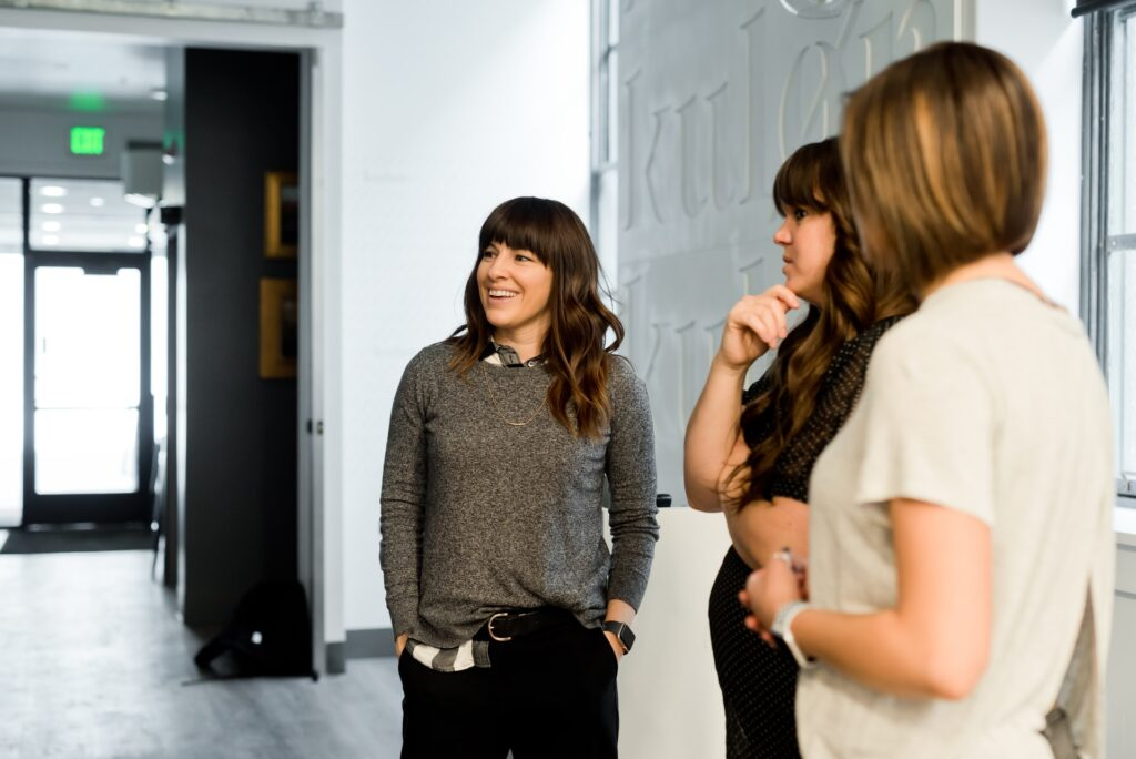 three women looking at image off screen in an office