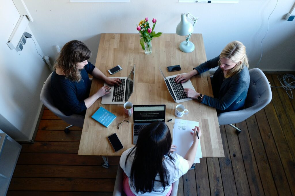 three women at table working on a business