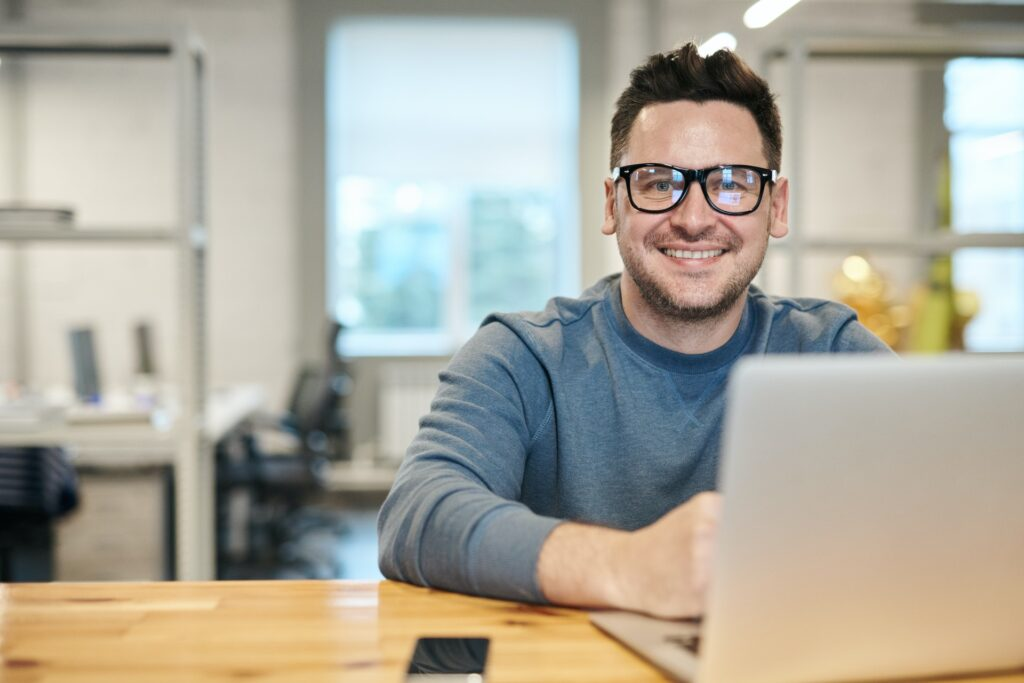 photo of a man sitting at his laptop in an office