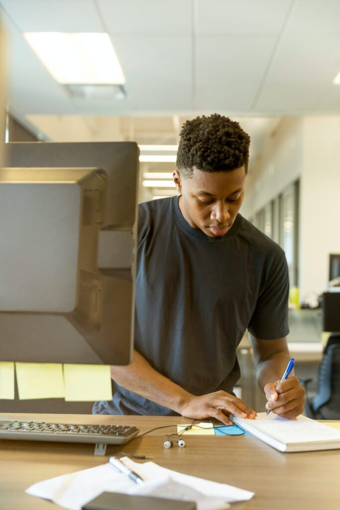 Man at computer station, standing up, entering journal entries in his Black owned business for a Black Business Month post