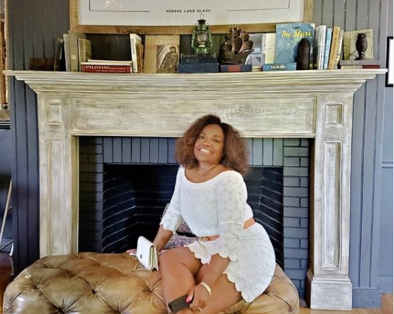 Nicole commissiong sitting on a chair in  front of a mantel