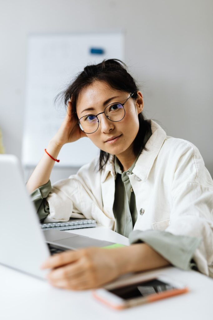 photo of a woman looking at a camera with her laptop in front of her, her hand on her head in blog article about the importance of employers taking care of their employees in order to survive post pandemic shortage