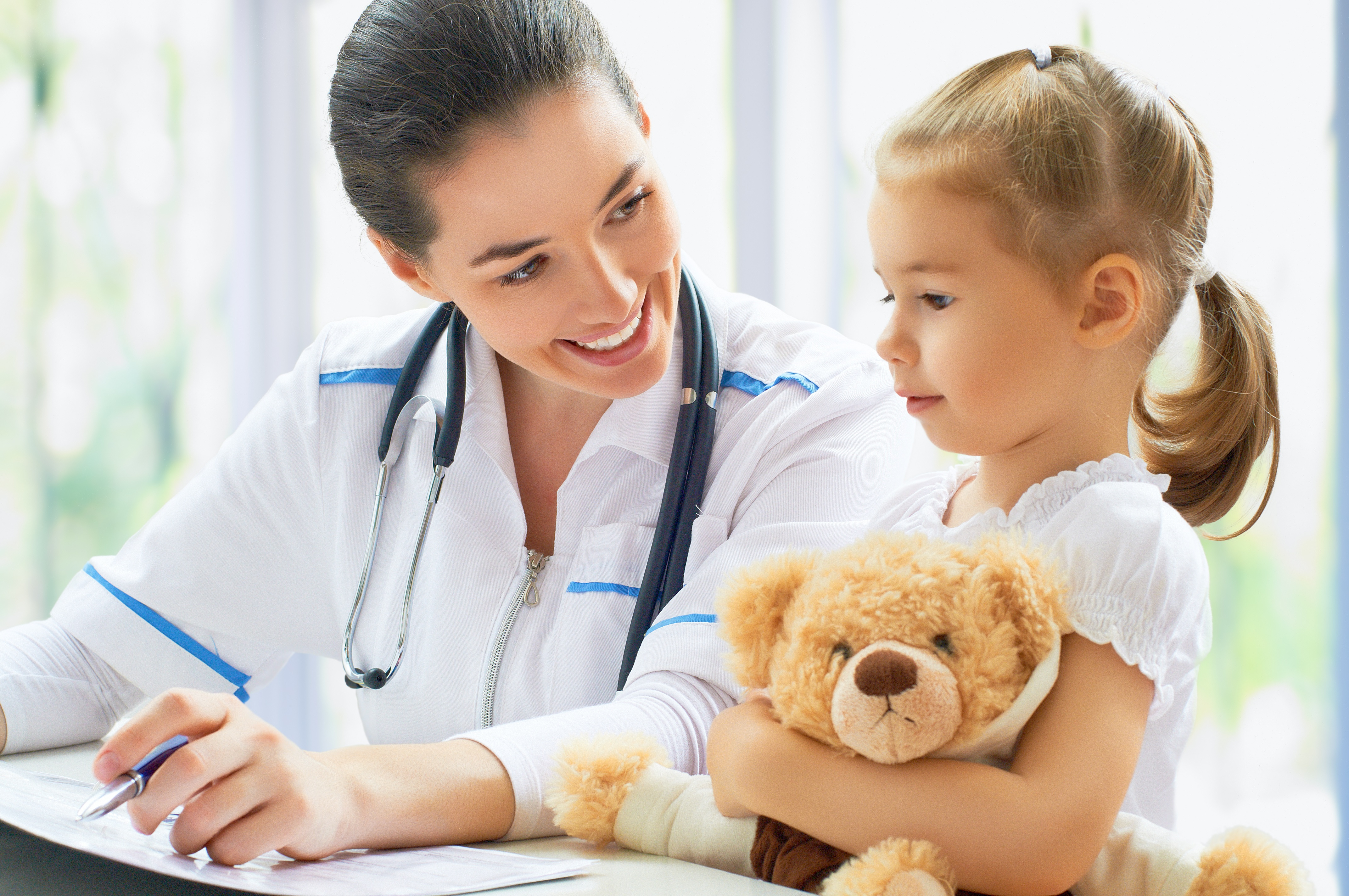 physician smiles at her young patient who is holding a teddy bear