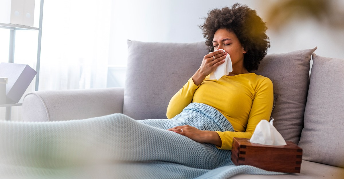 Young lady suffering from allergies at home on the couch.