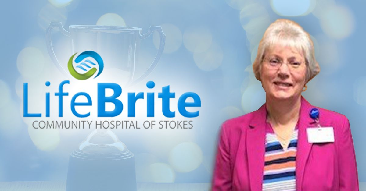 Trophy in background with LifeBrite Stokes logo with Pam Tilman in the foreground.