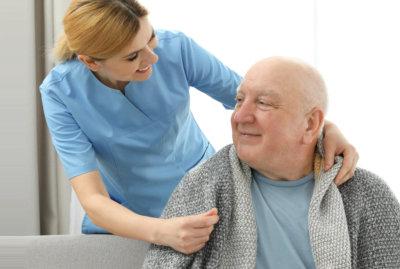 caregiver giving senior man a blanket