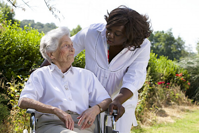 senior woman on wheelchair accompanied by her caregiver