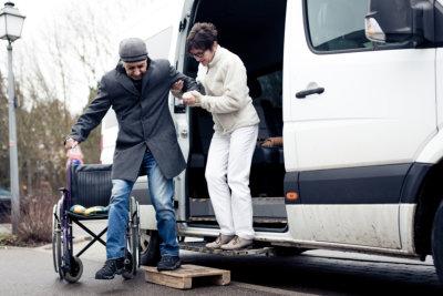 caregiver helping senior man get off the van