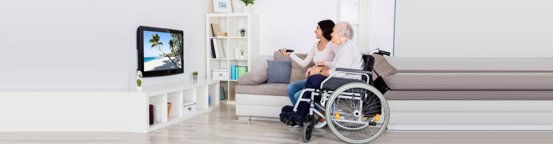 senior woman on wheelchair and caregiver watching television