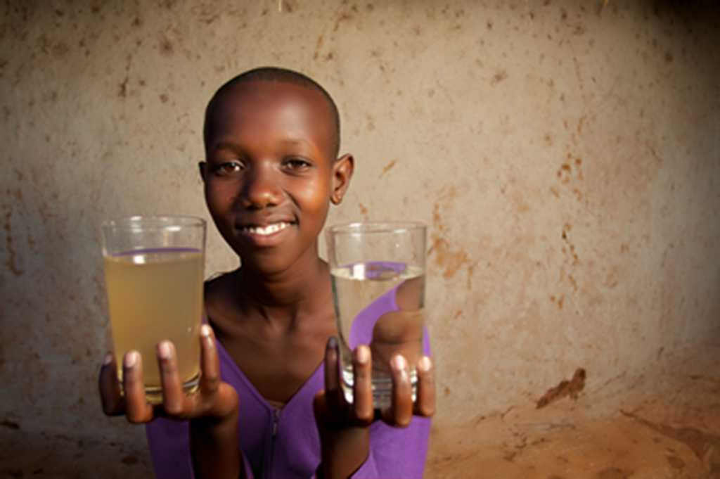 image of girl holding clean and dirty water in a glass