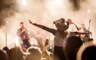 Woman dances on her friends shoulders during a concert in New Braunfels, TX.